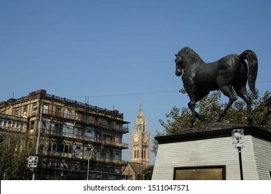 Mumbai; Maharashtra; India- Asia; Jan, 2017 : The statue of bronze sculpture 25 foot monument; has named the horse the 'Spirit of Kala Ghoda'. Iconic Horse   Rajabai clock tower in background