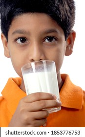 Mumbai; Maharashtra; India; Asia; June. 05; 2008 - Cute little indian boy holding glass of drinking milk keeping glass in his hand healthy concept