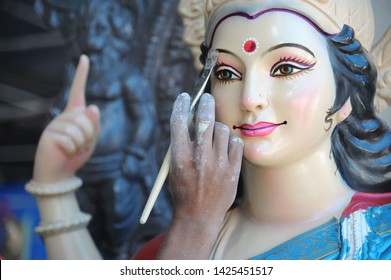 Mumbai; Maharashtra; India- Asia; Oct. 2013 : An artist gives final touches to Idol of Hindu Goddess Durga in workshop made of Plaster of Paris for upcoming navratri festival