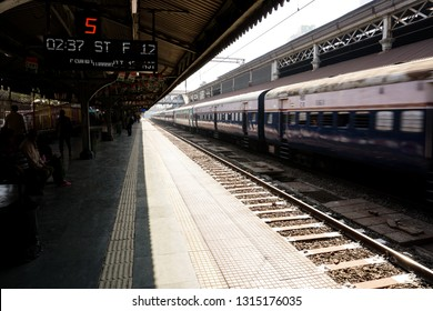 Mumbai, Maharashtra / India - January 29 2019: Train coming from distance, sunlight making lines on a train station. For Editorial use only.