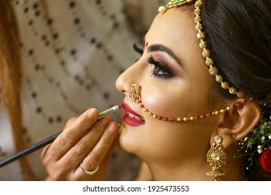Mumbai Maharashtra India July 06 2019 Selective focus wedding makeup artist making a makeup for bride Beautiful Indian bride getting ready Close-up of face Bridal makeup