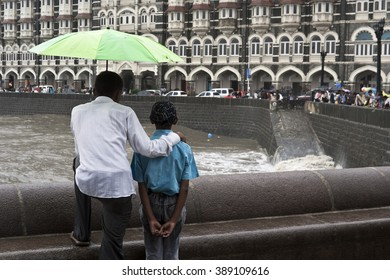 MUMBAI, MAHARASHTRA / INDIA - JUN 11, 2008 : A FATHER AND CHILD ARE LOOKING AT THE TAJ HOTEL DURING THE MONSOON IN INDIA.