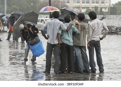 MUMBAI, MAHARASHTRA / INDIA - JUNE 11, 2008 : A PHOTOGRAPHER IS TAKING  THE PICTURES OF A GROUP OF YOUNG TOURISTS, COMES TO VISIT THE GATEWAY OF INDIA DURING THE MONSOON IN INDIA.