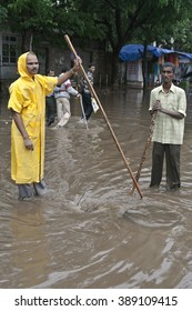 MUMBAI, MAHARASHTRA / INDIA - JUNE 7, 2008 : TWO MEN ARE CLEARING AND OBSERVING THE DRAINAGE FOR CLEARLY PASSING THE SUPPLY OF FLOOD WATER INTO DRAINAGE DURING THE MONSOON.