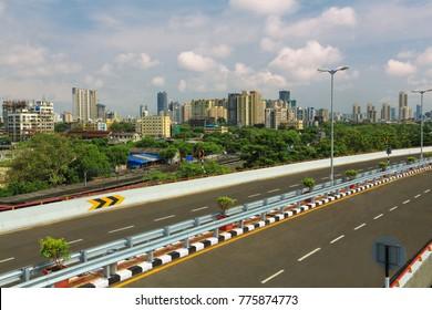 Mumbai, Maharashtra, India, ,June, 8,2013: Freeway tollfree flyover long stretch  elevated concrete bridge connecting Chembur suburb to Mumbai main city with township in background