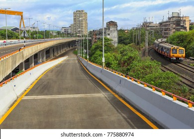 Mumbai, Maharashtra, India, ,June, 8,2013: Freeway tollfree flyover long stretch elevated concrete bridge adjacent to local rail line  connecting Chembur suburb to Mumbai  main city.
