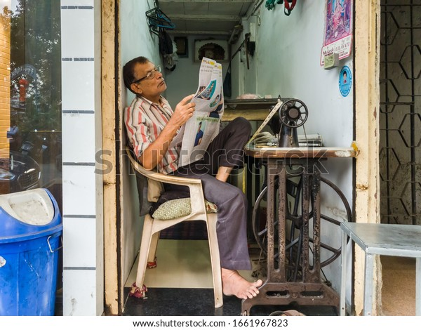 Mumbai, Maharashtra, India - November 2019: A candid street portrait of a tailor spends some idle time reading a newspaper beside his sewing machine inside his shop on the suburbs of the city.
