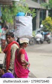 Mumbai, Maharashtra / India - October 13, 2017 : Lady carrying a bag at her head and a worker man in market