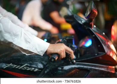 MUMBAI, MAHARASHTRA, INDIA - OCTOBER 5, 2017 - A closeup of a busy mototrbike rider on a Bajaj Pulsar (out of focus logo) bike.