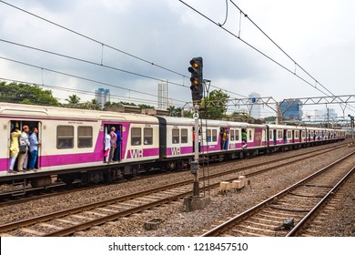 Mumbai, Maharashtra / India - September 13 2018: Local moving from one railway station to another with people traveling in it.