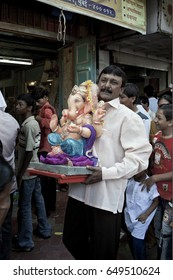 MUMBAI, MAHARASHTRA / INDIA - SEPTEMBER 15, 2007 : A MAN IS CARRYING ON HIS HAND THE STATUE OF A HINDU GOD SHREE GANESHA AND TAKING IT TO HIS HOME TO WORSHIP DURING THE GANESHA FESTIVAL.