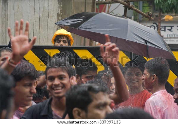 MUMBAI, MAHARASHTRA / INDIA - SUPTEMBER 3, 2009 : WORKER LOOKING TO THE CROWD PASSING BY THE ROAD DURING THE GANESH CHATURTHI FESTIVAL.