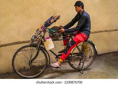 Mumbai, Maharashtra, January,31,2015: Street vendor moving door to door in suburbs with bycycle  mounted, pedal driven, knife sharpening wheel , Mumbai, Maharashtra ,India