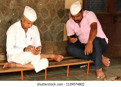 Mumbai, Maharashtra/India - 06/08/18; Two dabbawalas sitting on a bench taking a break and checking their mobile phone