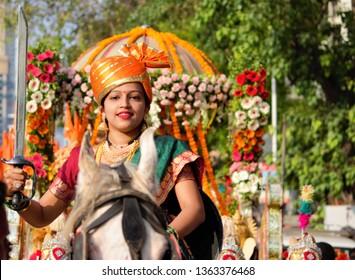 Mumbai, Maharashtra/India - April 6, 2019 : A young Marathi lady with a sword, riding a horse, leading the procession of people, celebrating Gudi Padwa/Ugadi - Traditional New Year Festival.