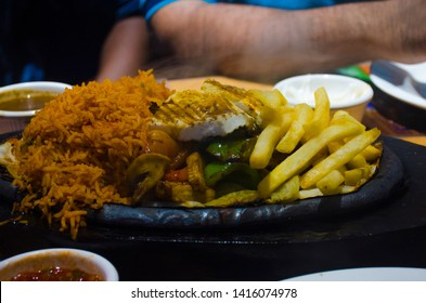 Mumbai sizzler plate full of rice , paneer and french fries.