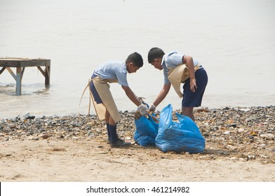 MUMBAI,INDIA, 23 SEPTEMBER 2010 : group of unidentified young students helping one another to clean up the Chaupati Beach in south Mumbai after Hindu festival of immersion of Ganesha into the sea ends