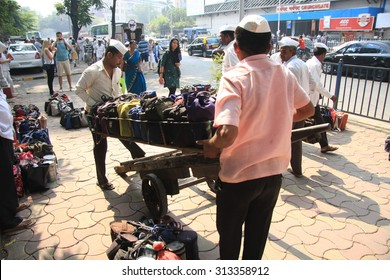 Mumbai/India - 24/11/14 - Dabbawala delivery at Churchgate Railway Station in Mumbai with two dabbawala's placing the tiffin carry crate on the ground