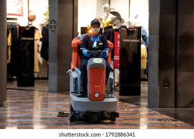 MUMBAI/INDIA - AUGUST 5, 2020: Worker wearing protective face masks operating a floor cleaning machine  inside a Phoenix Marketcity shopping mall after it reopened.