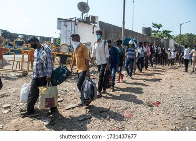 MUMBAI/INDIA - MAY 14, 2020: Crowd of migrant workers outside railway terminus for boarding a special train back home during a nationwide lockdown.
