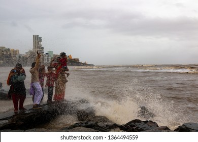 Mumbai,India,8-17-2018: A local family dangerously enjoying high tide sea waves on the edge of the sea during monsoon rains at Haji ali dargah,mosque . Rocks are dangerously slippery during rains