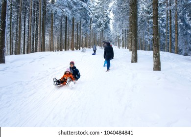MUMMELSEE, GERMANY - FEB 18, 2018: happy mother and daughter sleighing the sledding slope on a sunny winter day in Black Forest Germany