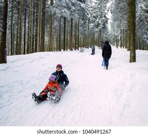 MUMMELSEE, GERMANY - FEB 18, 2018: Team happy mother and daughter sleighing the sledding slope on a sunny winter day