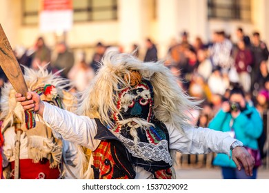 Mummers perform rituals to scare evil spirits at Surva festival at Pernik in Bulgaria. The people with the masks are called Kuker (kukeri). Woon mask and wood sword.