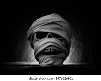 Mummy covered by clothes in skull decorated at halloween cosplay and light on dark background