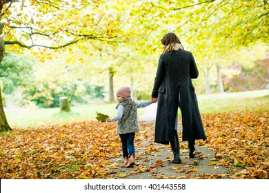Mummy and daughter having fun in a beautiful autumnal park
