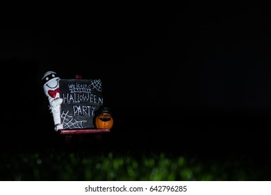 """Mummy Doll with Pumpkin Ghost Doll on Easel Blackboard with Message """"Welcome Halloween Party"""" Paperweight on Artificial Grass at Night. Copy Space for Text. Idea Concept for Halloween Background."""