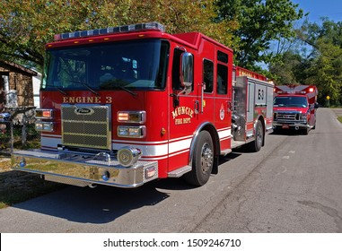Muncie, Indiana / United States - 9-19-19 - Fire Engine E-3 Driver side sharp angle on  city street with EMT ambulance behind and trees and blue sky