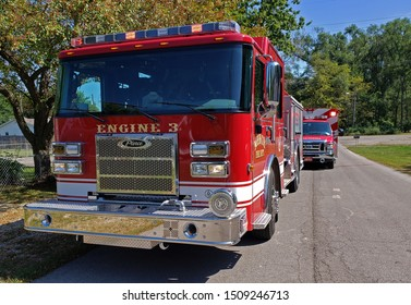 Muncie, Indiana / United States - 9-19-19 - Fire Engine E-3 Driver side sharp angle on street with EMT ambulance behind and trees and blue sky
