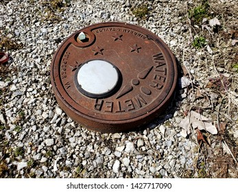 Muncie,Indiana / United States 6-17-2019: Rusted round metal water meter cover surrounded by gravel