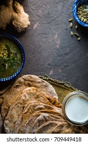 Mung bean soup and chapatti on the dark background vertical