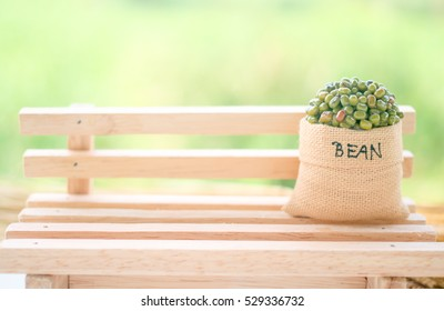 Mung beans and almond in bag on wood chair with garden background