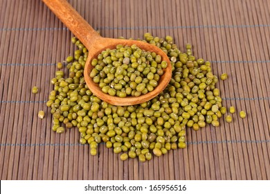 Mung beans over wooden spoon on color background