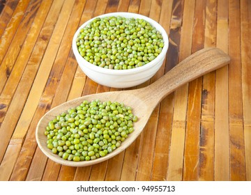 mung beans over wooden spoon on wood background