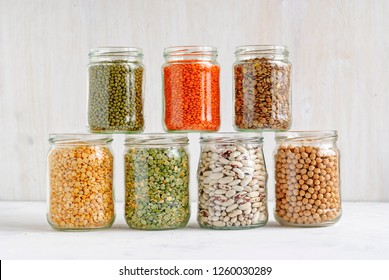 Mung beans, peas, beans, lentils and chickpeas in stacked glass storage jars over a white wall background rich in protein, dietary fiber and vitamins