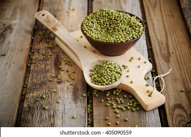 Mung beans in a spoon on a wooden table