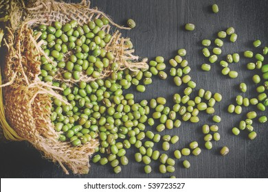 Mung beans (Vigna radiata) spilling from burlap bag on black wooden background. Top view