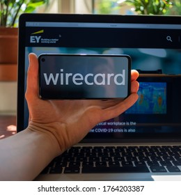 Munich. Bavaria / Germany -06 26 2020: Wirecard. Logo of company on mobile screen with Ernst & Young web site in the background.