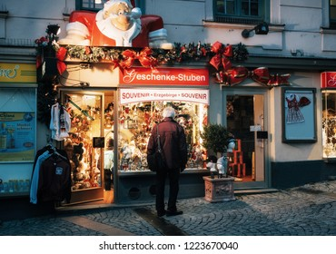Munich, Bavaria, Germany - December 6, 2017: Lonely senior man looks at decorated shop window with gifts on Christmas eve at night.