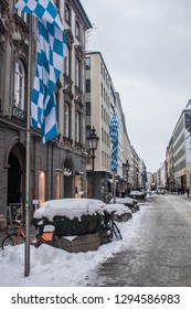 Munich, Bavaria / Germany - January 12 2019. Theatinerstrasse in winter with snow and bavarian flags.