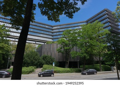 "Munich, Bavaria, Germany - July 05, 2020: building of the ""European Patent Office"", in front framed by the leaf of green trees"