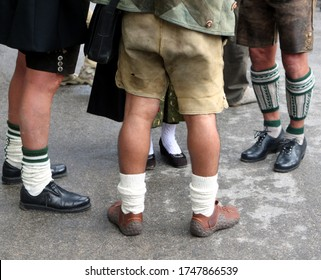 """Munich, Bavaria / Germany - July 19, 2009: legs of three men and a woman wearing traditional bavarian costumes """"Lederhosen"""", shoes and  """"Dirndl"""" at the barn dance """"Kocherlball"""" in the english garden"""
