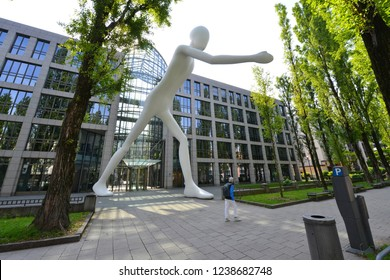 Munich, Bavaria / Germany - May 19, 2018: Walking Man by Jonathan Borowsky in front of Headquarters of Munich RE in Munich, Germany - Munich Re is one of the world's leading reinsurers
