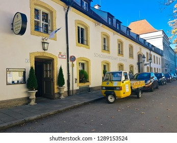 MUNICH, BAVARIA, GERMANY - October 14, 2017:  Bavarian restaurant Schlosswirtschaft Schwaige Nymphenburg in the baroque palace grounds of the Schloss Nymphenburg. Cute 3 wheel mini truck our front.