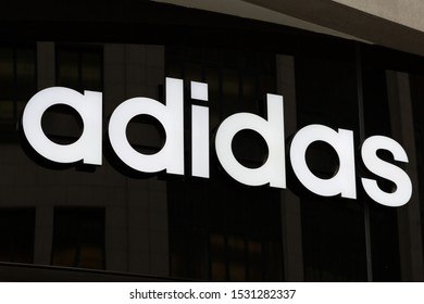 MUNICH, BAVARIA / GERMANY - October 2, 2019: Close up of Adidas logo and writing. White letters on black background. The company is the worldwide second largest manufacturer of sportswear.