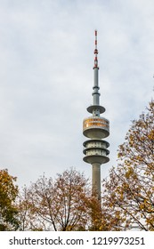 Munich, Bavaria / Germany - October 30 2018. Olympic Tower in fall with cloudy sky and trees with autumn leaves.